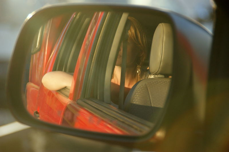 Reflection of woman sitting in car on side-view mirror