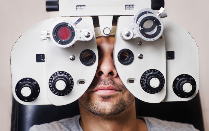 Optometrist store, young man in horopter Agtis Close Up Eye Eye Test Equipment Lenses Men Optician Opticians Optometrist Optometry Phoropter Sky Test Vision