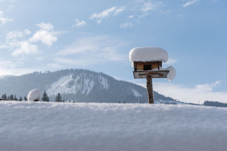 Homemade wooden bird's feeder in winter, under snow. mountain and cloudy sky at the background