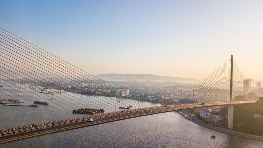 View of suspension bridge against sky in city