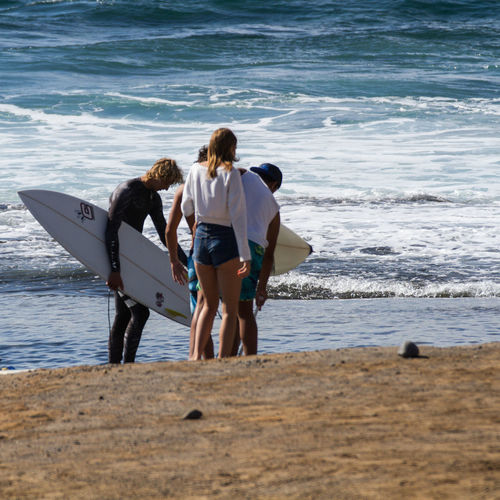 Surfers with friends standing on shore at beach