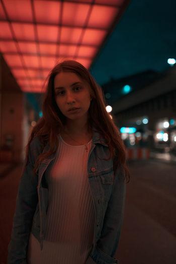 Portrait of woman standing on footpath under illuminated lights