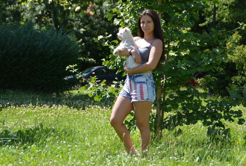 American Flag Casual Clothing Dog Enjoyment Front View Full Length Fun Grass Green Color Growth Happiness Leisure Activity Lifestyles Outdoors Pants Person Pet Portrait Smiling Tree Young Women Pet Portraits