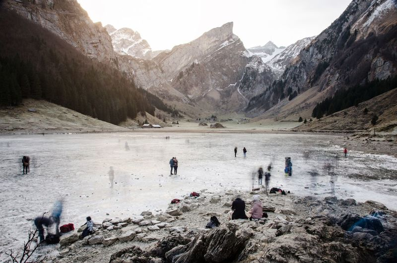 People at frozen lake against mountains