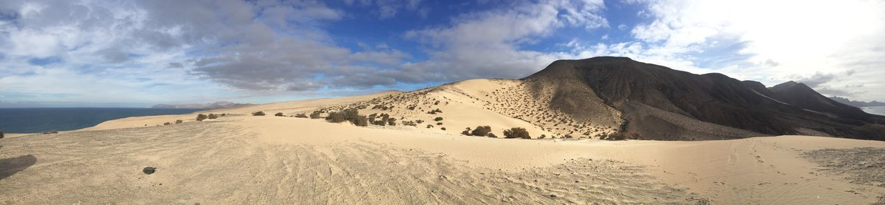 Panoramic view of desert area against cloudy sky