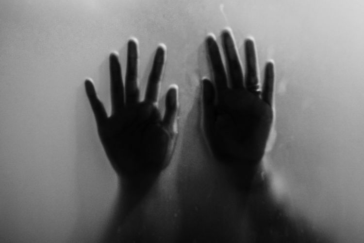 Close-up of hands touching window