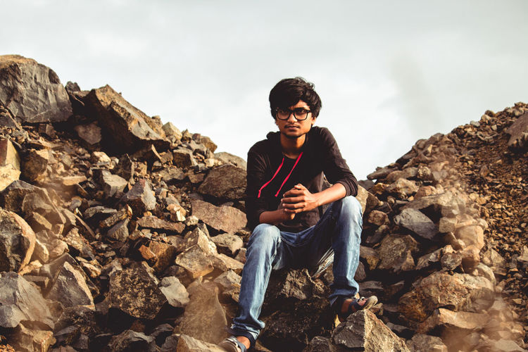 Young man sitting on rock