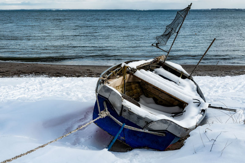 Boat moored on shore by sea against sky