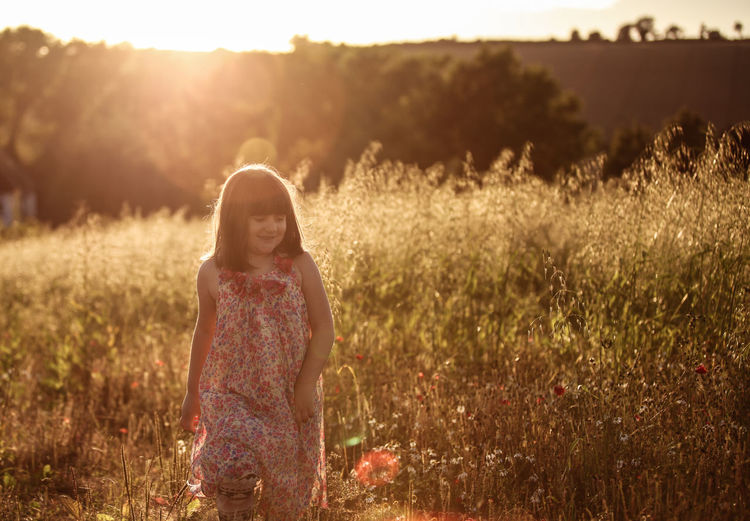 Full length of young girl standing on grassy field