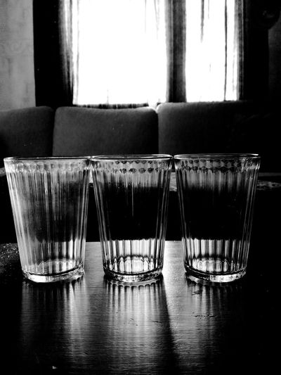 Indoors  No People Table Day Glasses Transparency Light And Shadow Dark And Light In Front Sun Through The Window Foreground Focus Blackandwhite Drinking Glasses Used After Party Sofa Curtains Used Glass Day After  Trio See Through Close-up Still Life Round Shapes