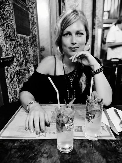 Portrait of woman drinking glass on table at restaurant