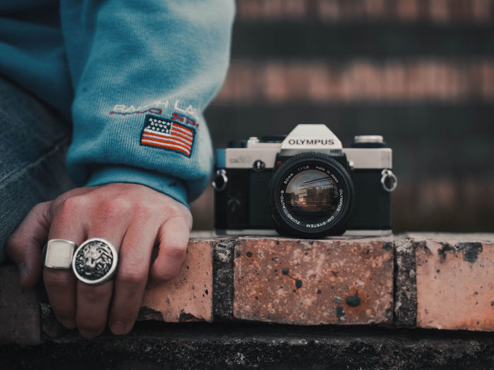 Close-up of hand holding camera against blurred background