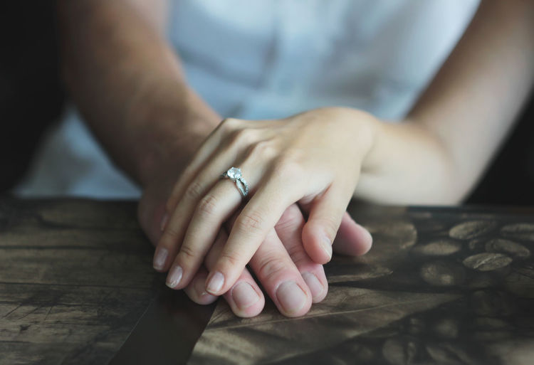 Woman's hand with an engagement ring on man's hand, date in the cafe Couple Date Lifestyle Adult Body Part Close-up Engagement Ring Finger Focus On Foreground Hand Human Body Part Human Finger Human Hand Indoors  Jewelry Midsection Nail Nail Art One Person Real People Ring Ring Of Kerry Table Women