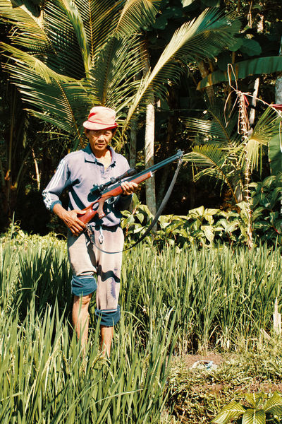 Gun Hunter Adventure Beauty In Nature Day Full Length Fun Grass Guns Leisure Activity Nature One Person One Woman Only Outdoors Palm Tree People Plant Portrait Real People Riffle Smiling Standing Tree