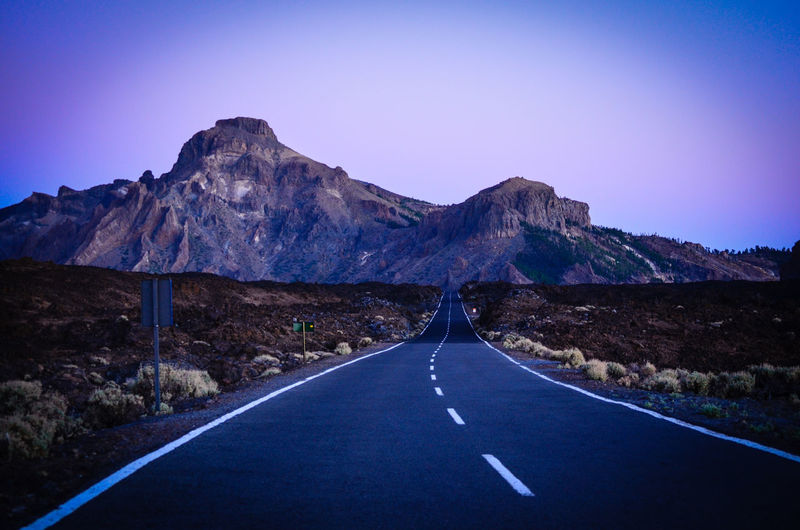Empty road leading towards rocky mountains against sky during sunset