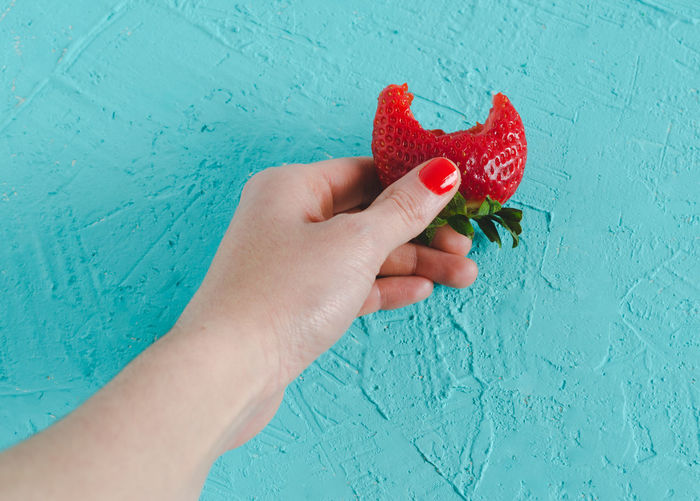 Hand holding a ripe strawberry on blue lay. Copy Space Writing Advertisement Berry Fruit Bluebackground Body Part Finger Food Food And Drink Fruit Hand Healthy Eating Holding Human Body Part Human Hand Leisure Activity Lifestyles One Person Personal Perspective Real People Red Strawberry Unrecognizable Person Wall - Building Feature Wellbeing