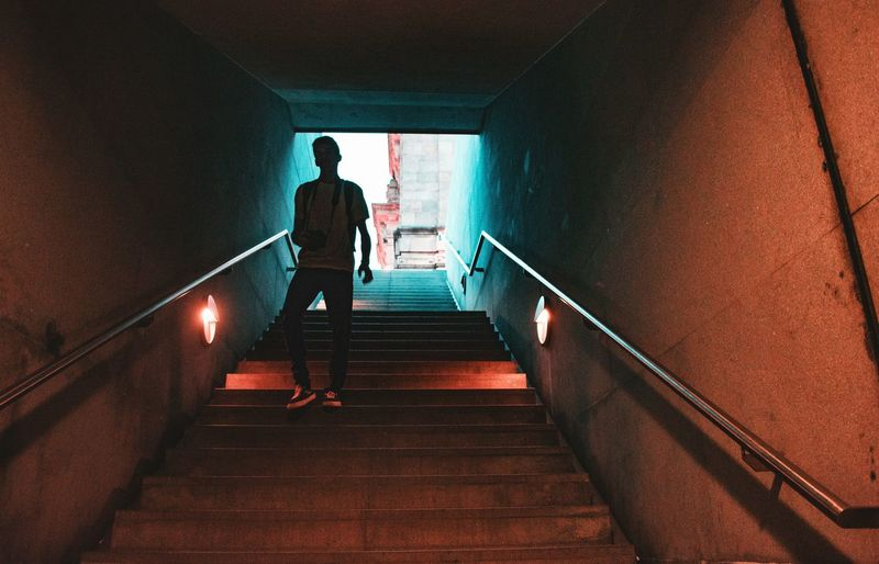 Low angle view of young man moving down on steps