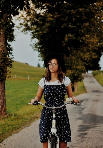 Woman with bicycle standing on footpath against trees