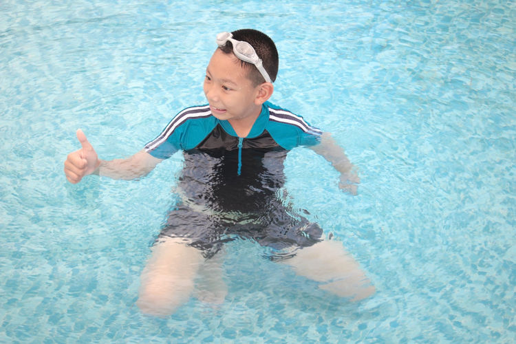 High angle view of boy showing thumbs up in swimming pool
