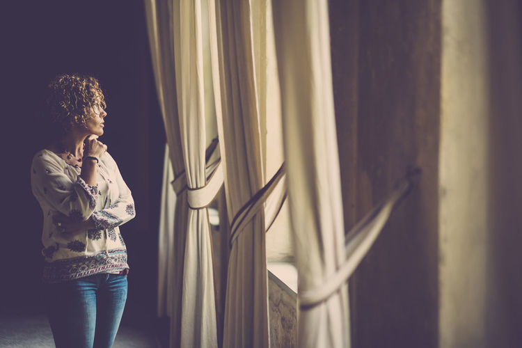 woman thinking in front of the window Casual Look Looking Out Serenity Thinking Ancient House Casual Clothing Curly Hair Curtains Cute Day Home Interior Indoors  One Person People Real People Relaxation Romantic Place Shadow Solitude Standing Window