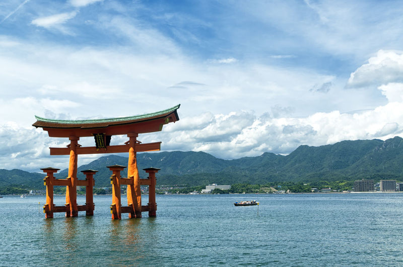 View of the torii (gate) of Itsukushima Shrine at high tide floating in the water of the island of Miyajima, Hiroshima Prefecture, Japan. Unesco World Heritage Site Shrine Shinto complex Antique Asian  Gate Japan Japanese  Miyajima Pray Torii Gate Architecture Belief Buddhism Hiroshima Itsukushima Pilgrim Religion Sacred Shinto Shrine Sky Temple Tide Unesco Water Waterfront Wooden