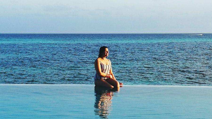 Woman sitting poolside against sea