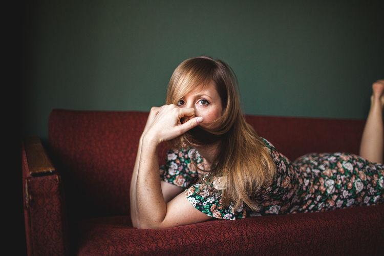 Portrait of woman sitting on sofa