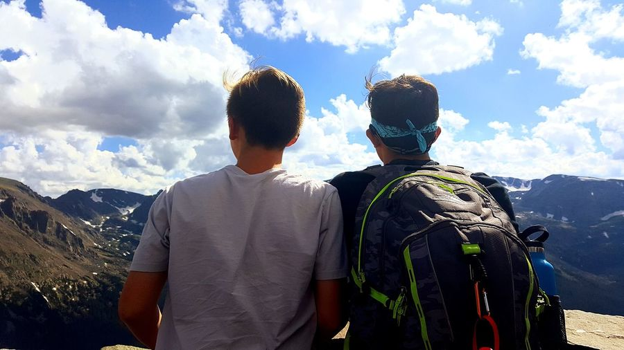 Rear view of friends with backpack standing at observation point against sky