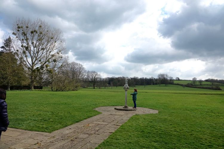 Side view of man on grassy field against sky
