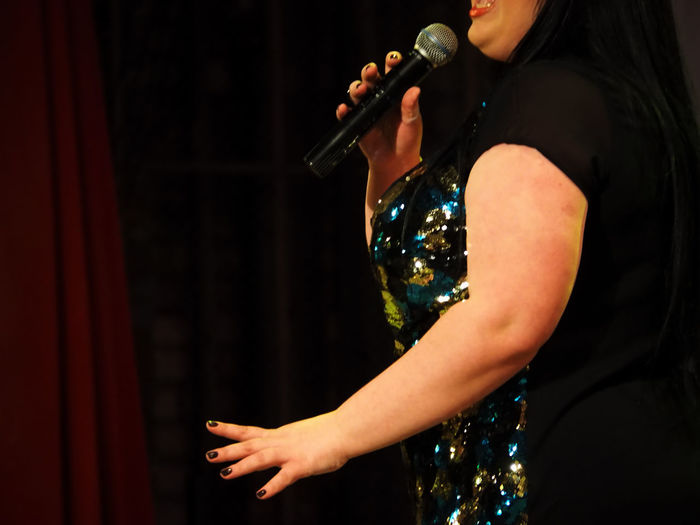 Midsection of woman singing on stage