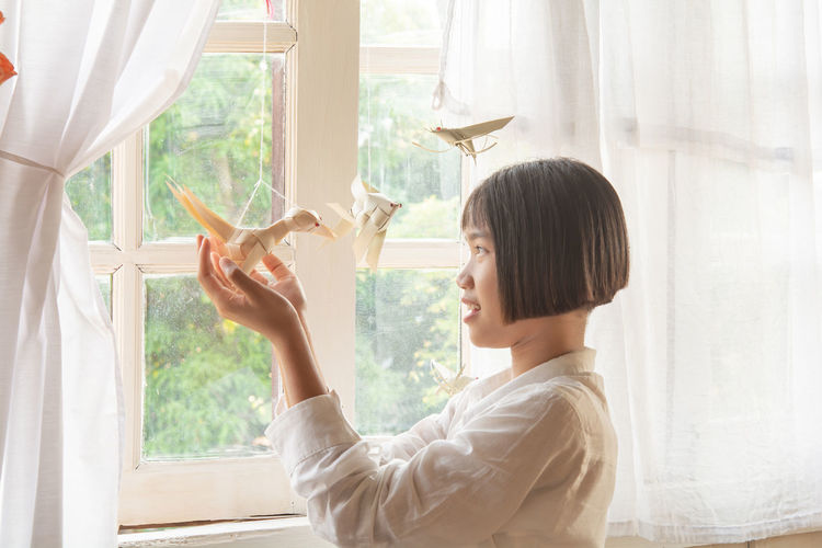 Profile view of girl holding by artificial bird by window
