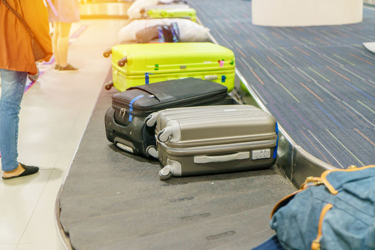 Low section of women standing by suitcases on conveyor belt at airport