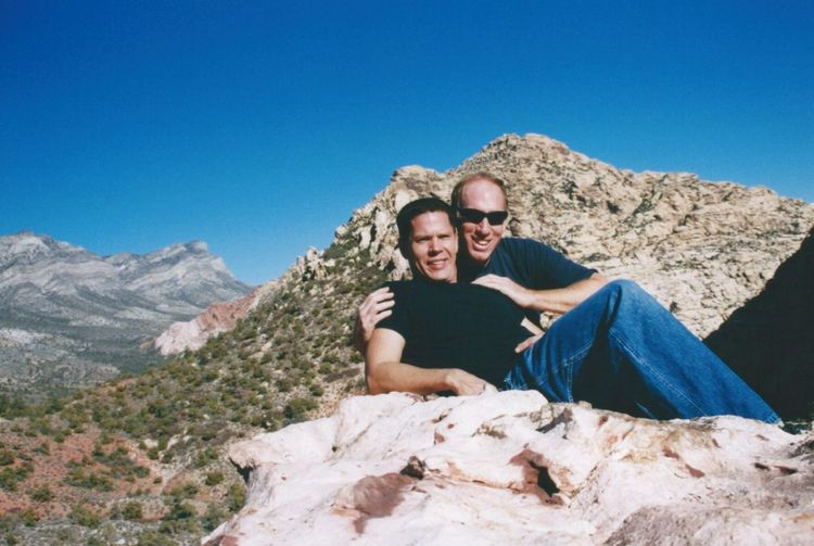 Portrait of father and son resting on rocky mountain against clear blue sky