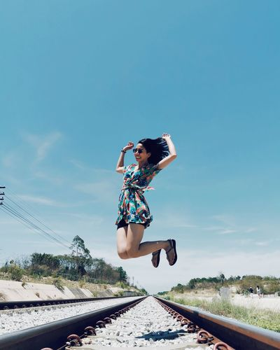 Full length of woman jumping on railroad track against sky