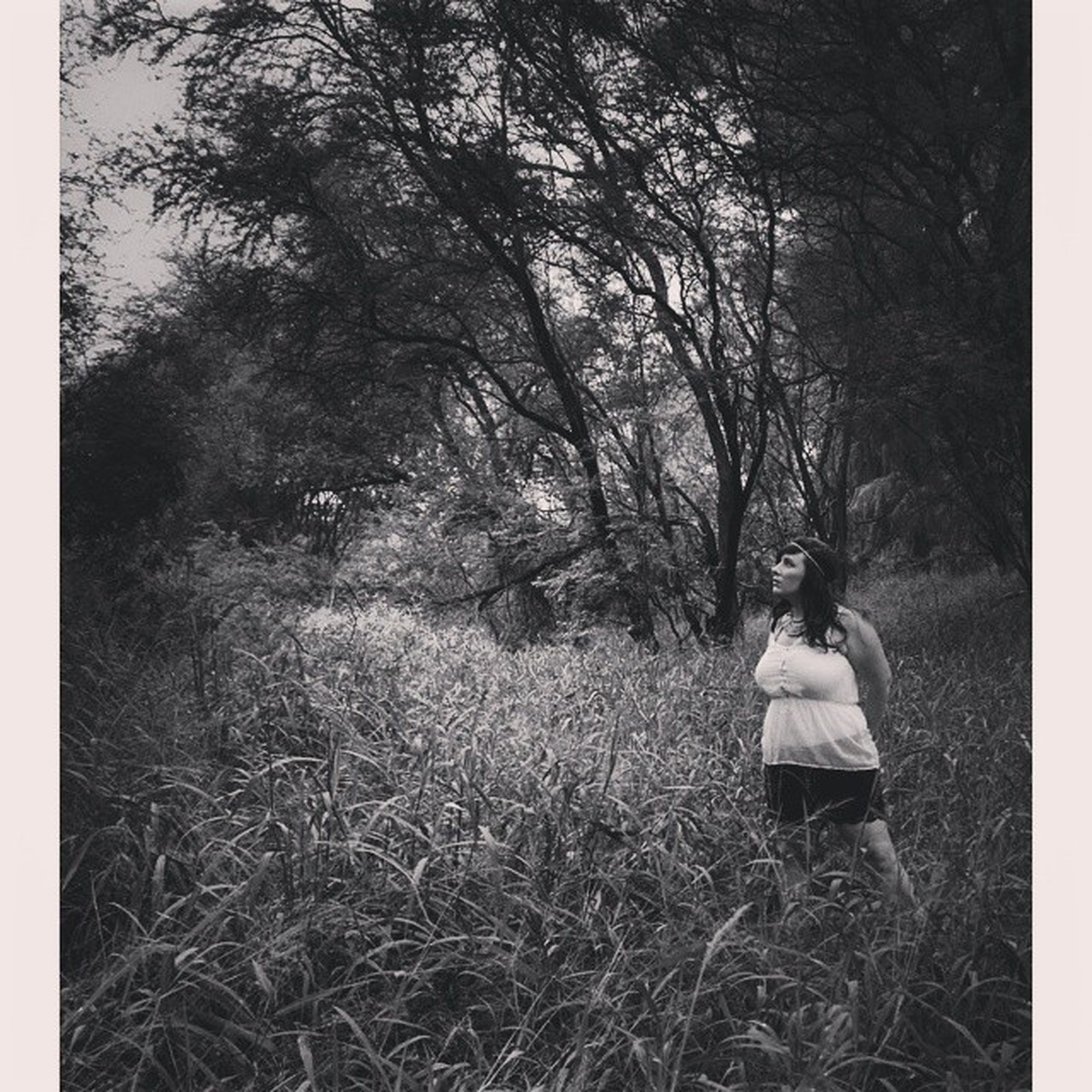 grass, tree, field, lifestyles, rear view, leisure activity, full length, bare tree, tranquility, childhood, standing, growth, nature, landscape, tree trunk, casual clothing, day, grassy