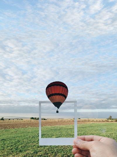 Man holding hot air balloon against sky