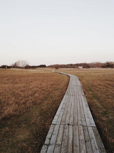 Wooden boardwalk leading towards field against clear sky