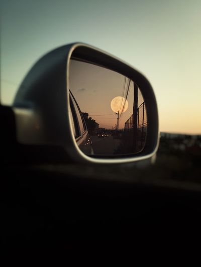 Close-up of moon reflecting on car side-view mirror