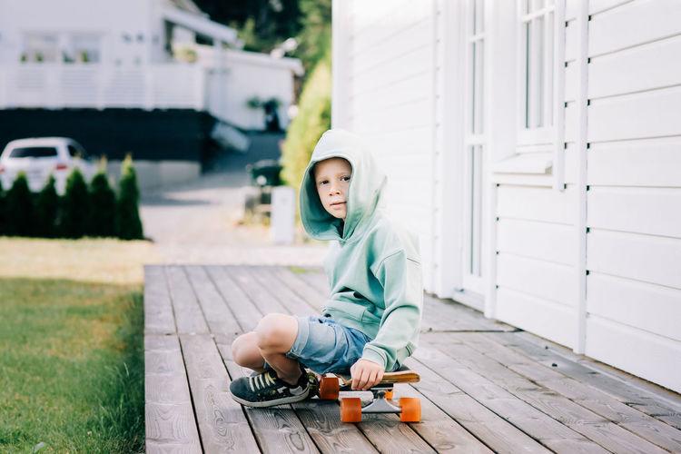 Full length of boy sitting outdoors