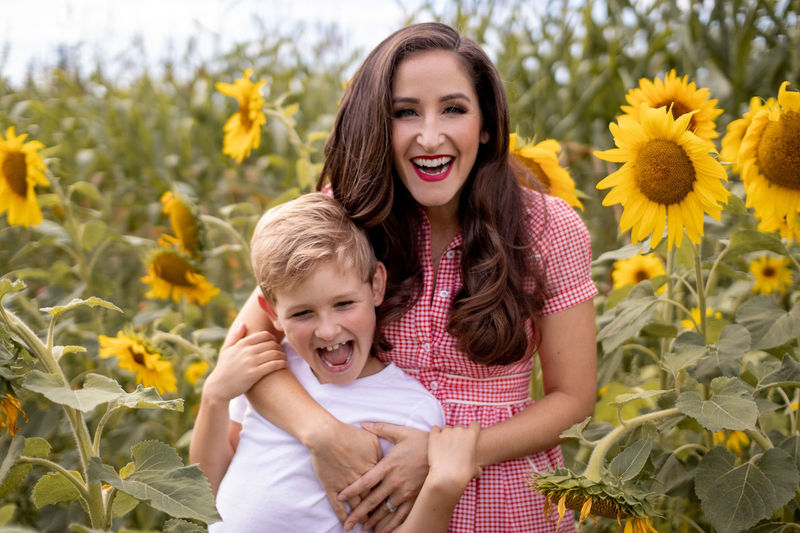 Portrait Of Happy Mother And Son Standing Against Sunflowers