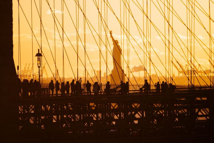 Silhouette people visiting statue of liberty during sunset