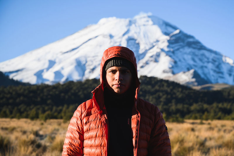 Portrait of man standing against snowcapped mountains during winter