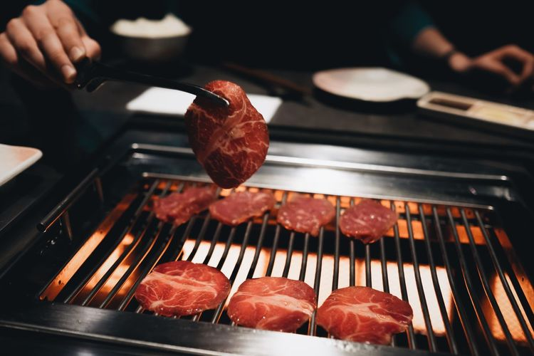 Cropped image of person cooking meat on barbecue grill
