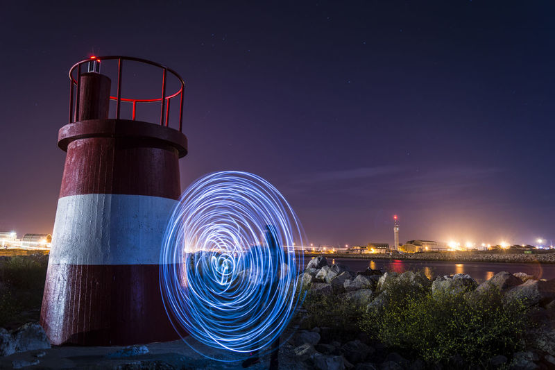 Person light painting by lookout tower against sky at night