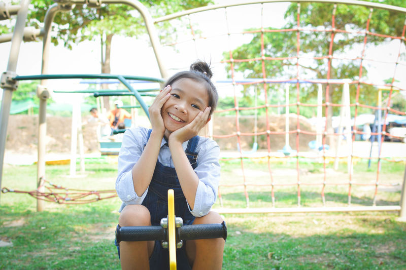 Portrait Of Girl Sitting On Spring Ride At Park