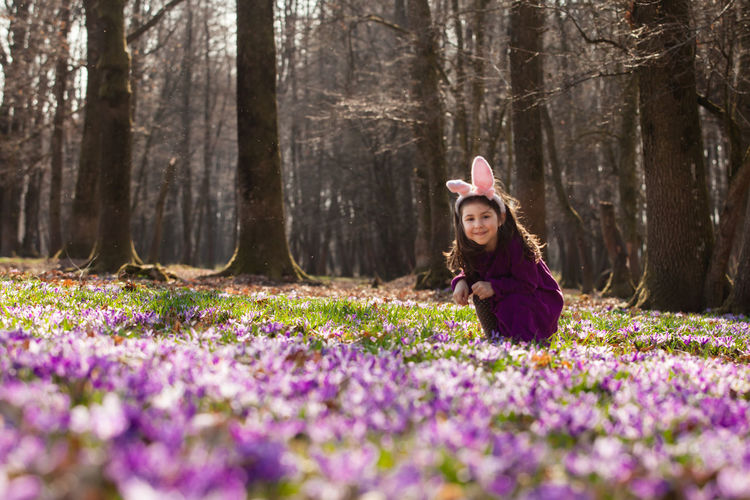 Portrait of smiling woman sitting by purple flowers in forest