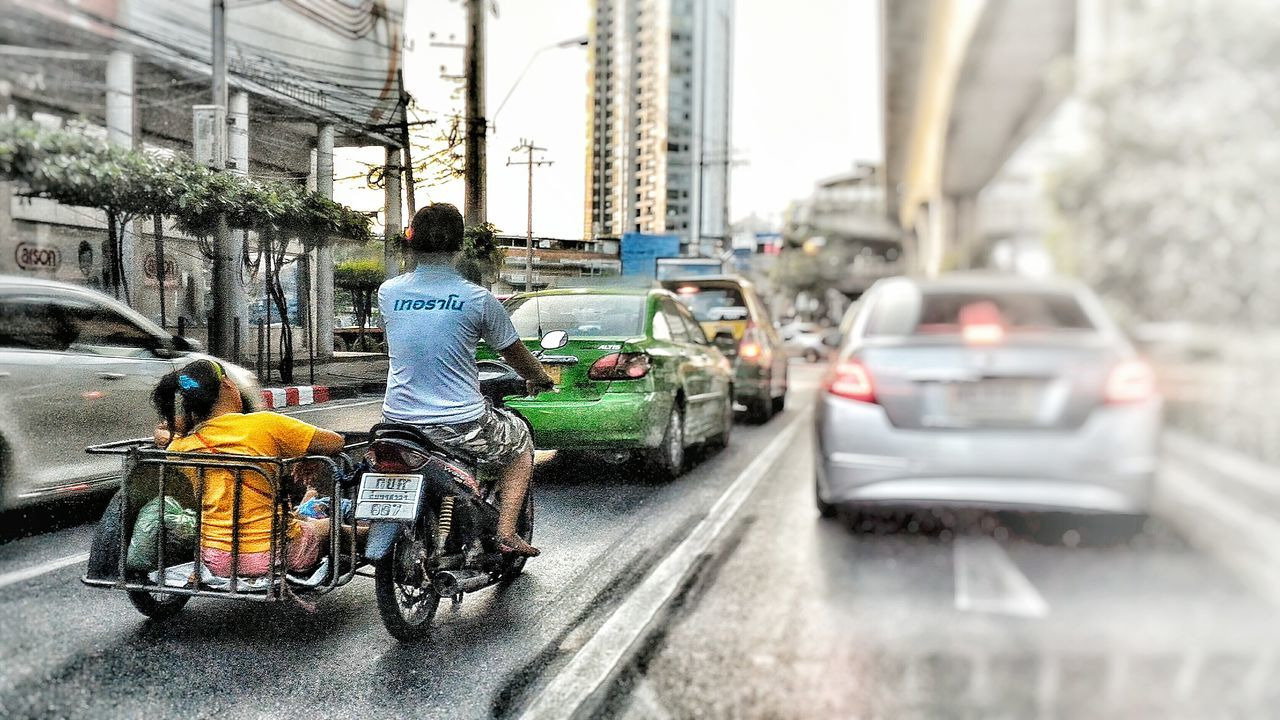 transportation, car, land vehicle, mode of transport, real people, architecture, street, rear view, built structure, two people, men, bicycle, building exterior, day, city, outdoors, lifestyles, togetherness, women, people