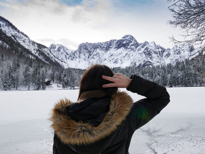 Woman from behind, snowcapped mountain against sky, winter.