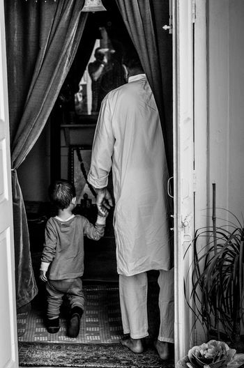 Rear View Of Grandfather And Grandson At Home