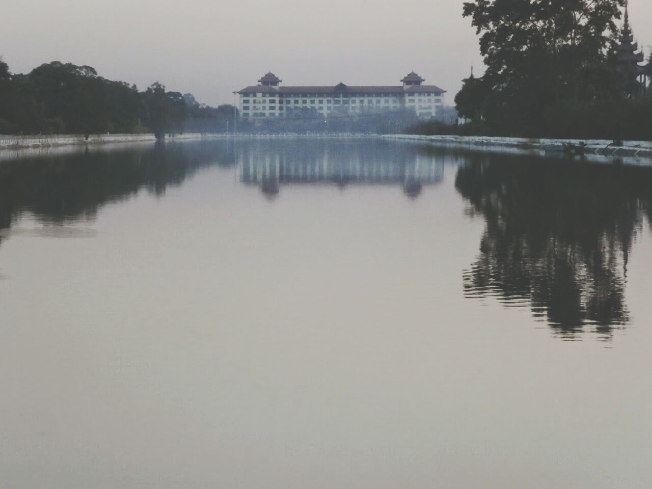 Calm Lake By Building Against Sky